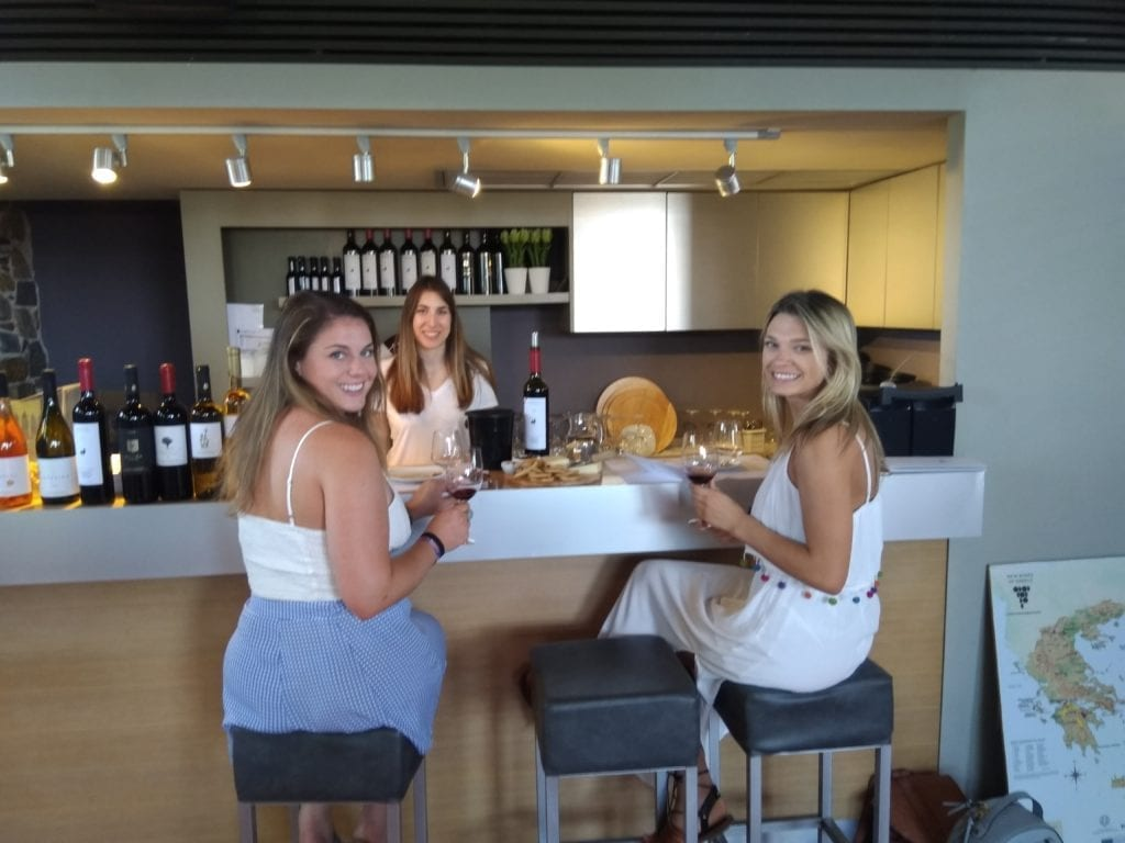 two girls smile having wine tasting